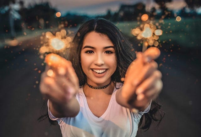 a woman, glowing, holding sparklers