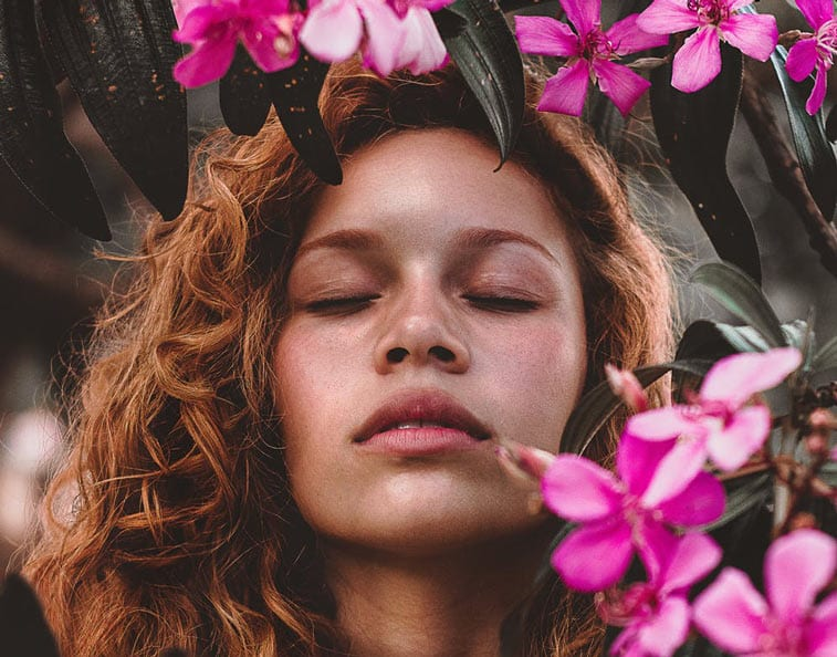 a woman breathing in a forest of flowers