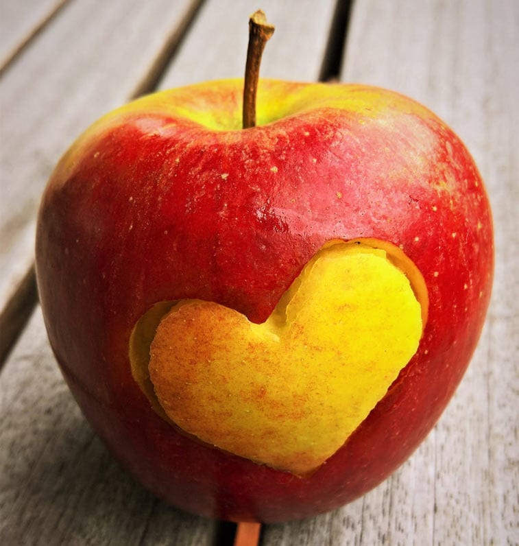 an apple with a heart cut into the skin