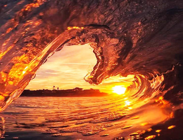 a curling wave forms a heart shape against the sunrise