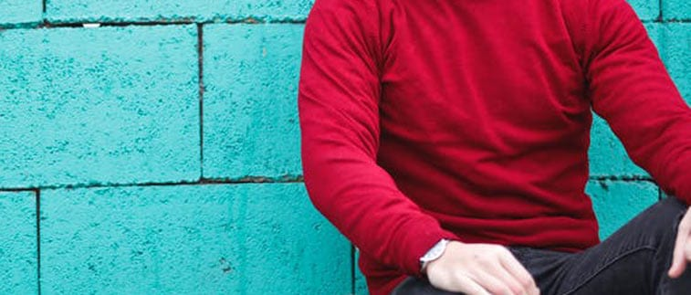 a man in a red sweater against a blue brick wall
