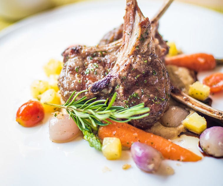 a dinner comprised of lamb, carrots and other vegetables