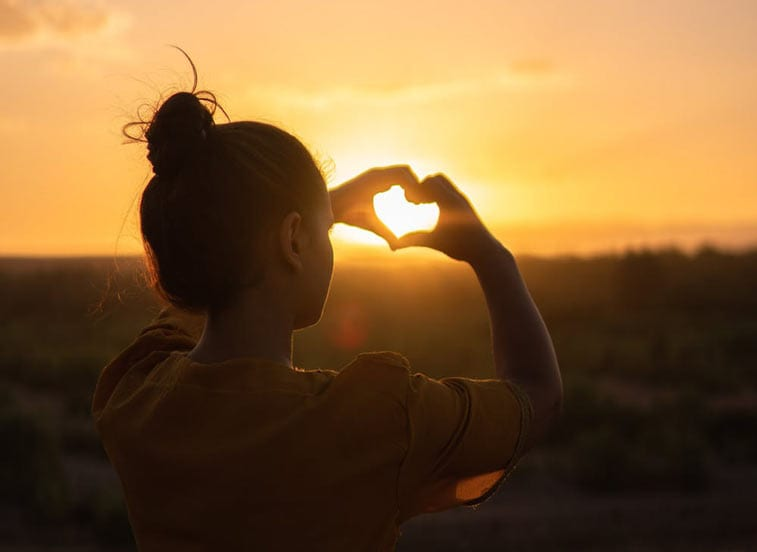 a woman holds her hand to form a heart, the sun shining through it