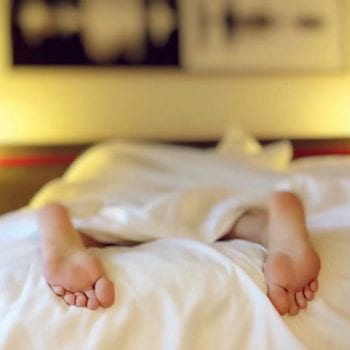 feet poking out of bed sheets