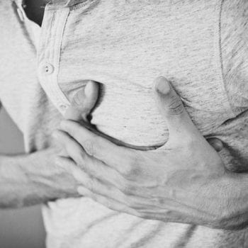 man with shingles pain clutches chest