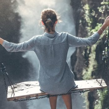 a woman on a swing over a waterfall