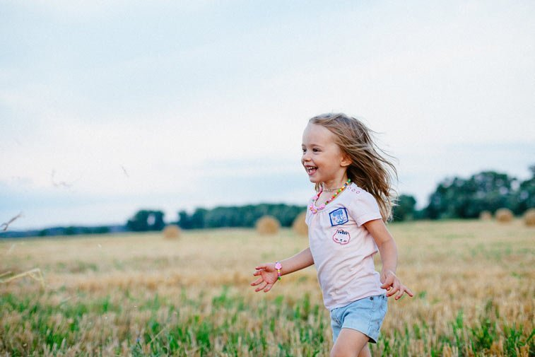 a young girl runs through a field