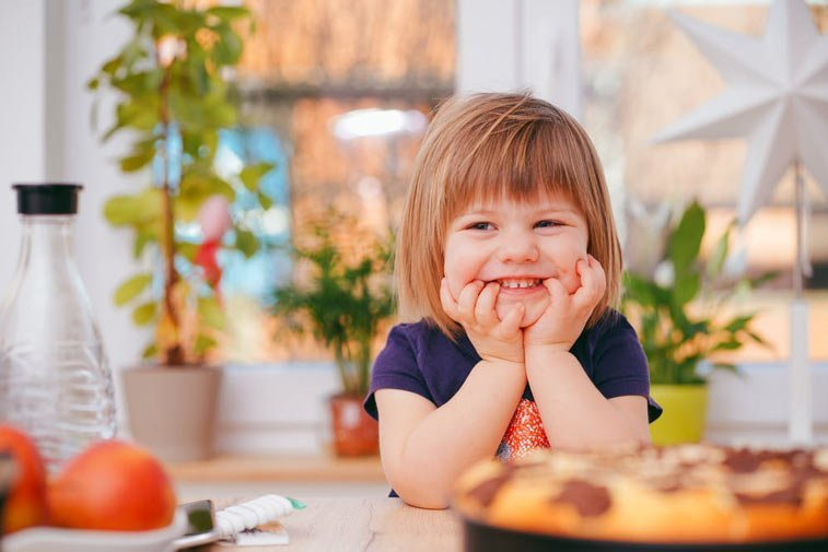 a young girl smiling at the dinner table