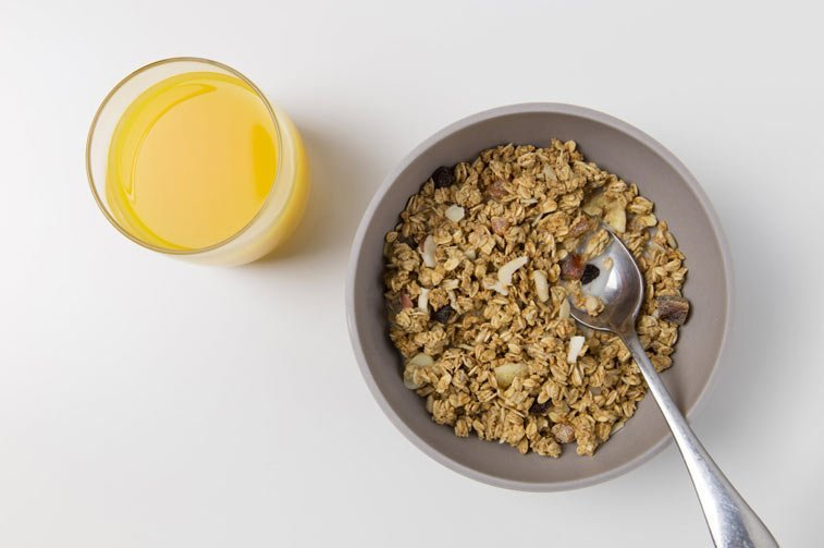 a bowl of grain cereal and a glass of orange juice