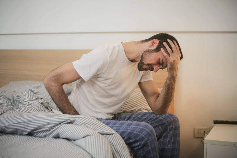 a man in bed suffering from fatigue